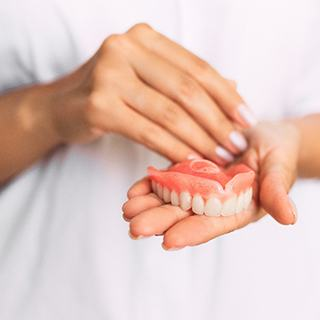 Female dentist holding a denture for the upper arch