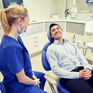 man in light blue dress shirt smiling at dentist