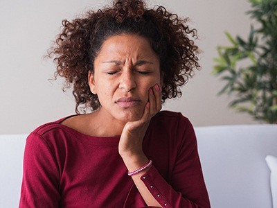person holding their mouth due to pain caused by gum disease