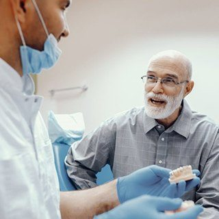 An older patient asking about implant-retained dentures.