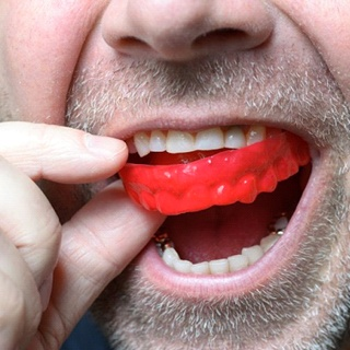 close up of man putting red mouthguard into his mouth