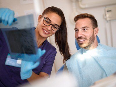 Dental team member and man looking at x-rays